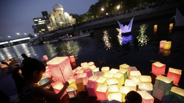 Children offer prayers Thursday after releasing paper lanterns to the Motoyasu River, where tens of thousands of atomic bombing victims died, with the backdrop of the Atomic Bomb Dome in Hiroshima.