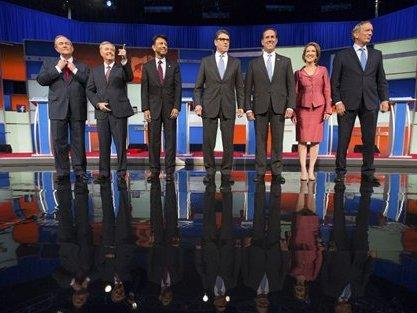 Republican presidential candidates from left, Jim Gilmore, Lindsey Graham, Bobby Jindal, Rick Perry, Rick Santorum, Carly Fiorina, and George Pataki take the stage for a pre-debate forum at the Quicken Loans Arena, Thursday, Aug. 6, 2015, in Cleveland. S