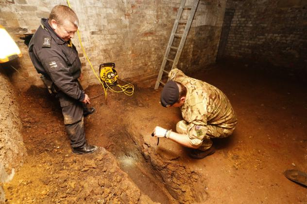 Military bomb disposal experts examine an unexploded German bomb from World War II in East London. Hundreds of residents were moved out for their safety.