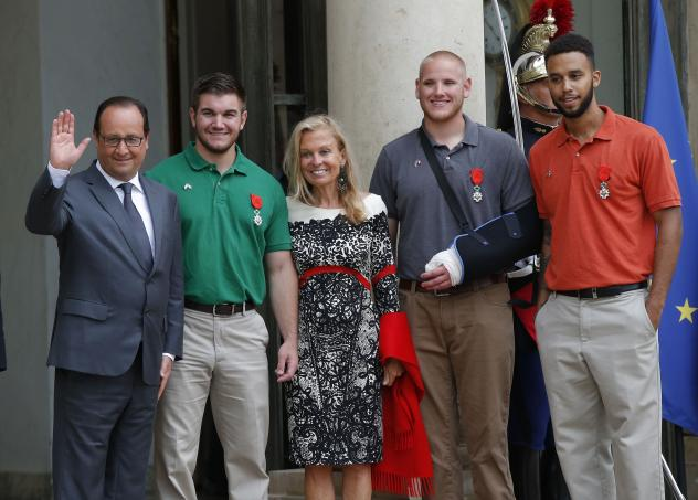 French President Francois Hollande and U.S. Ambassador to France Jane D. Hartley stand with (from left) Alek Skarlatos, Spencer Stone and Anthony Sadler as they leave the Elysee Palace in Paris. The three American men, along with a British citizen, were