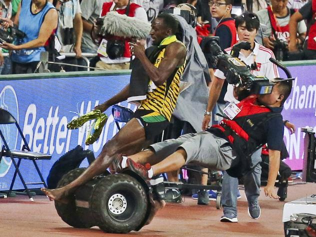 Usain Bolt of Jamaica is hit by a cameraman on a Segway while celebrating his win in the 200-meter final during the 15th IAAF World Championships at National Stadium in Beijing.