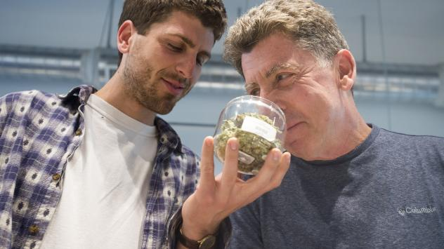 Two men inspect the goods at at Farma, a marijuana dispensary in Portland, Oregon. The state's first week of retail sales brought in an estimated $11 million, a trade group says.