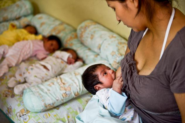 A woman breast-feeds her child as she waits to donate milk to a milk bank in Lima. The donations are used for babies whose mothers can't provide breast milk.