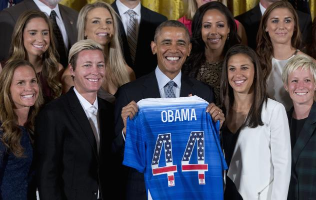 President Obama poses with a jersey he received from the U.S. Women's National Soccer Team during a ceremony to honor the team and their victory in the 2015 FIFA Women's World Cup. Standing with Obama are (from left) Christie Rampone, Morgan Brian, Abby