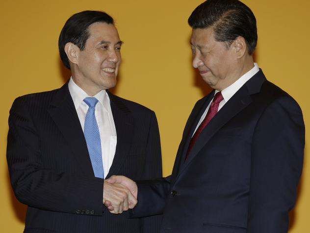 Chinese President Xi Jinping, right, and Taiwanese President Ma Ying-jeou, left, shake hands at the start of a historic meeting. The moment marks the first top-level contact between the formerly-bitter Cold War foes in 66 years.