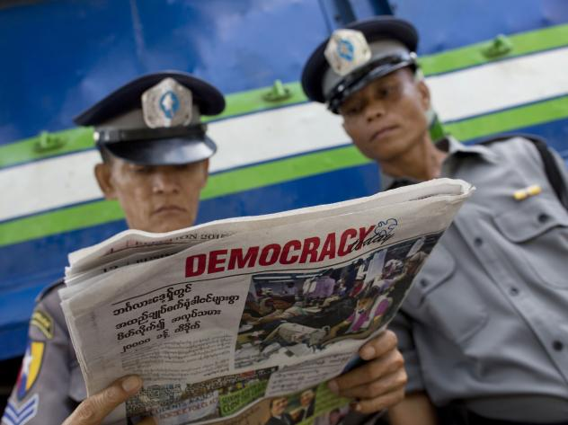 On Wednesday in Yangon, Myanmar, two police officers read about the elections that saw opposition leader Aung San Suu Kyi's party win a majority of seats in parliament.