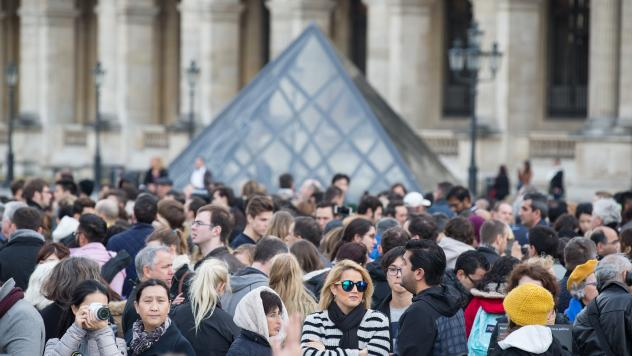 Tourists wait to visit the Louvre as it reopens in Paris on Monday. As the city tries to recover from Friday's attacks, people who planned to travel there seem to be conflicted about whether to go.