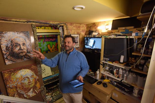 Pindar Van Arman in his studio with paintings created by his bitPaintr portrait-painting robot.