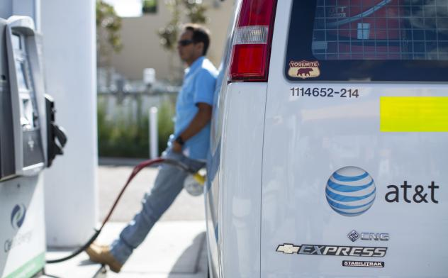 Prices for both gasoline and natural gas have fallen this year. An AT&T employee fills up his company van in San Diego last month.