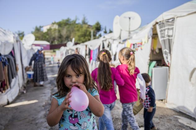 A Syrian refugee girl plays with her balloon at a camp in Turkey.