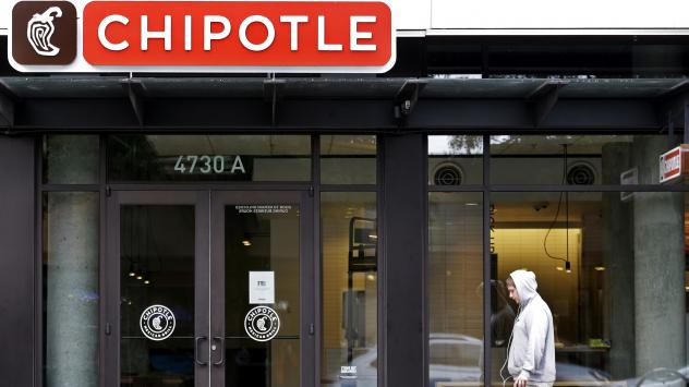 A passerby walks past a Chipotle restaurant in Seattle in November that closed following one of two <em>E.coli</em> outbreaks that sickened scores of people.