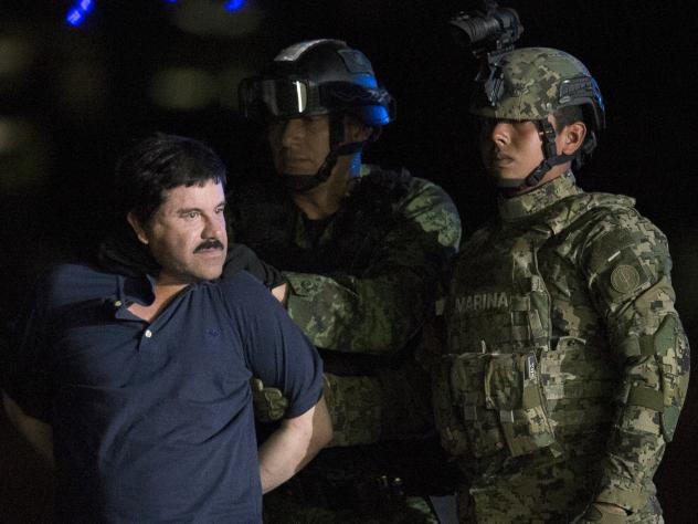 """Mexican drug kingpin Joaquin """"El Chapo"""" Guzman, escorted by army soldiers to a waiting helicopter, at a federal hangar in Mexico City on Friday."""