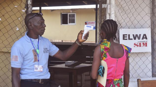 A unidentified family member (right) of a 10-year-old boy that contracted Ebola has her temperature measured by a health worker outside an Ebola clinic on the outskirts of Monrovia, Liberia, on Nov. 20. Liberia, Guinea and Sierra Leone have now gone 42 d