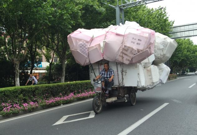Men driving piles of plastic foam to recycling transfer stations are a common sight in Shanghai, but it's a tough way to make a living because prices are low.