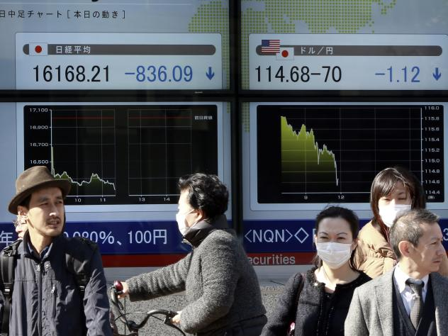 Pedestrians stand outside a securities firm in Tokyo Tuesday. Stocks plunged again in Japan, and the interest rate on the benchmark bond fell below zero.
