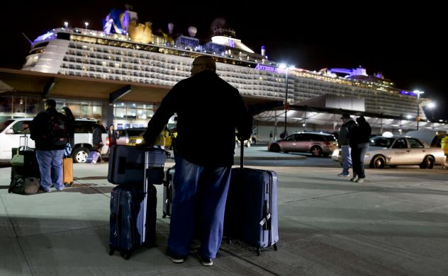 A passenger from the Royal Caribbean cruise ship Anthem of the Seas waits for transportation after arriving at the Cape Liberty cruise port in Bayonne, N.J., Wednesday. The ship was forced to turn around after hitting a strong storm at sea.