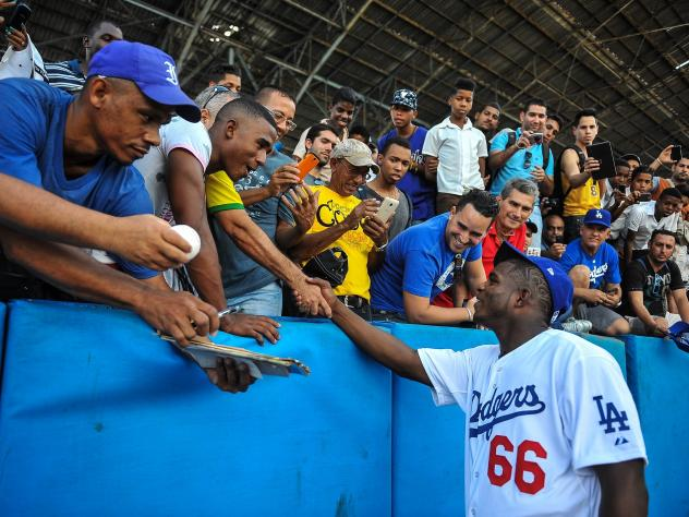 Los Angeles Dodgers star Yasiel Puig shakes hands with fans Dec. 16 at the Latin American Stadium in Havana during a Major League Baseball goodwill tour. Puig and fellow Cuban national Jose Abreu of the Chicago White Sox returned home Tuesday for the fir