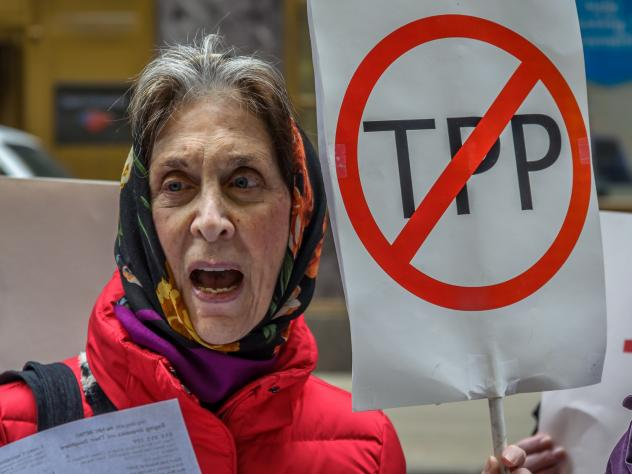 "A protester holds a ""STOP THE TPP"" sign outside the New Zealand embassy in New York, where activists protested the TPP deal."