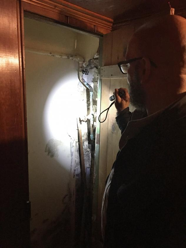 Hector Moreno checks a basement for lead paint in Baltimore. He is an environmental assessor with Green and Healthy Homes.