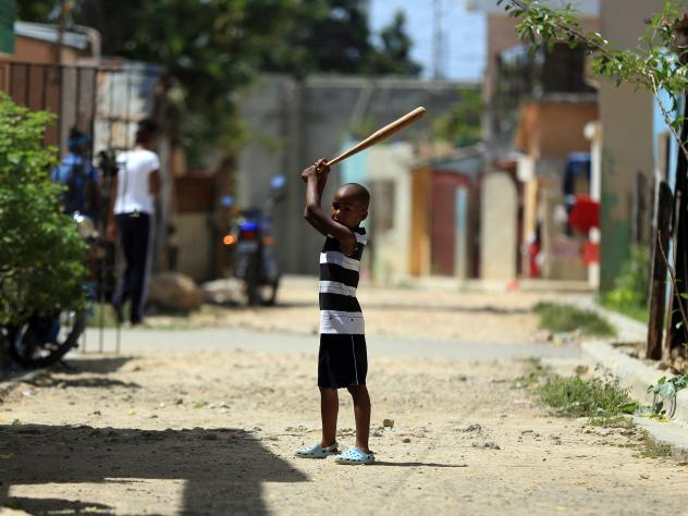 A boy is ready to take a swing on the streets of San Pedro de Macoris, capital of the Dominican Republic.