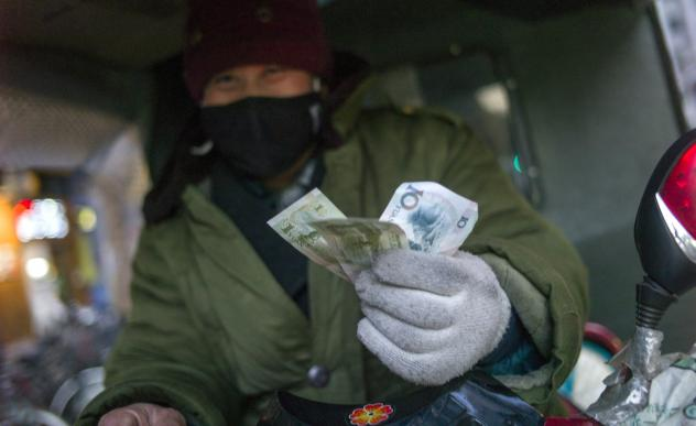 A driver holds up his change from a transaction in Beijing in February. The latest World Economic Outlook offers some good news for China's economy this year.