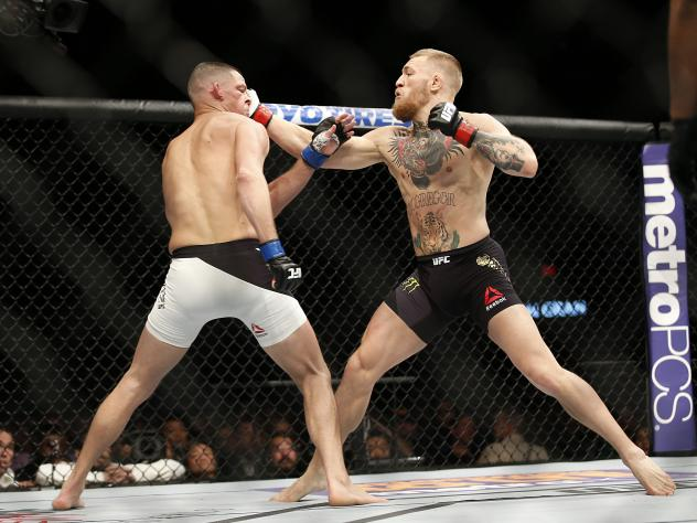 Conor McGregor (right) trades punches with Nate Diaz (left) during their UFC 196 welterweight mixed martial arts match on March 5. Diaz won in the second round.