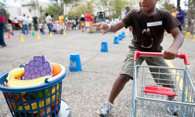 """A child runs a shopping cart relay during an Education Department summer enrichment event, """"Let's Read, Let's Move."""" The 2012 event was part of a summer initiative to engage youths in summer reading and physical activity, and provide them information abo"""