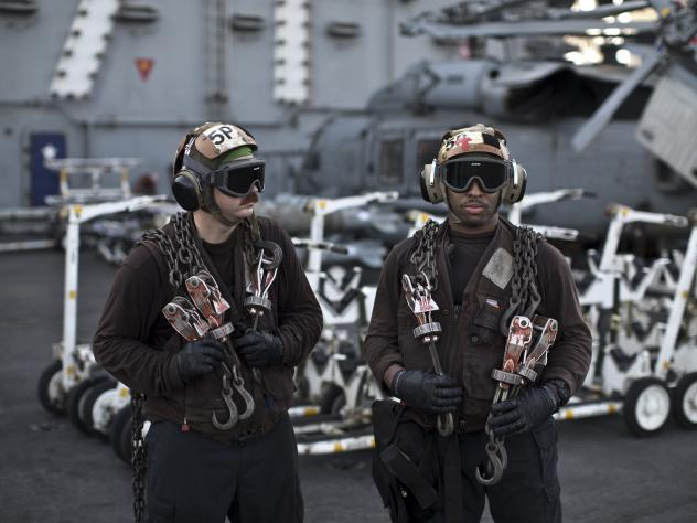 U.S. Navy air wing captains pause on the flight deck of the aircraft carrier USS Theodore Roosevelt last September. Every day, the steam-powered catapult aboard this massive ship flings American fighter jets into the sky, on missions to target the extrem