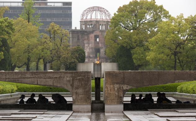 Visitors shelter from the rain under the Peace Flame as they visit the Memorial Park and the nearby Hiroshima Peace Memorial Museum on April 21 in Hiroshima, Japan. The dome in the background was destroyed during the attack, and preserved as a monument.