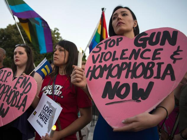 Mourners hold up signs during a vigil in Washington, D.C. in reaction to the mass shooting at a gay nightclub in Orlando, Fla.