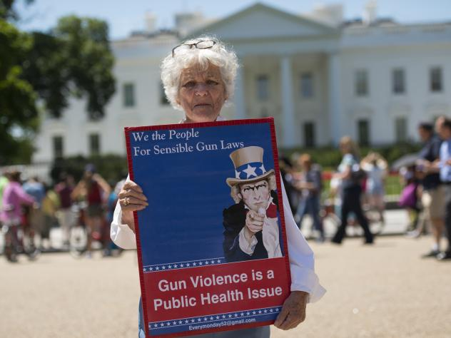 A woman walks with a sign to protest gun violence and call for sensible gun laws outside the White House on Monday.
