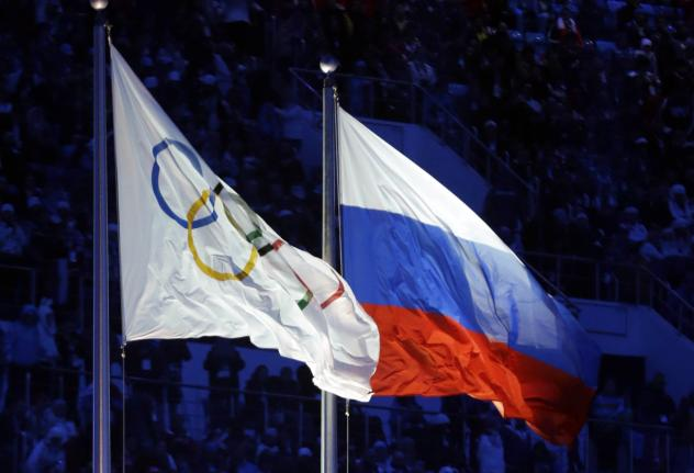 The Russian and the Olympic flags wave during the opening ceremony of the 2014 Winter Olympics in Sochi, Russia.