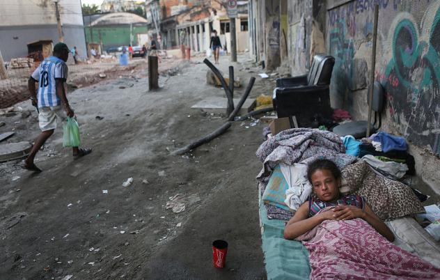 """Vanessa, currently homeless, rests on a Rio de Janeiro street on Friday where construction of a new light rail system has been delayed. The state government of Rio de Janeiro today declared a state of """"calamity"""" ahead of the Rio 2016 Olympic Games which"""