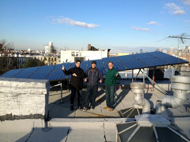 Eric Frumin (right) stands in front of his solar panels on the roof of his Brooklyn home alongside architect David Cunningham (left) and AeonSolar's Allen Frishman (center).