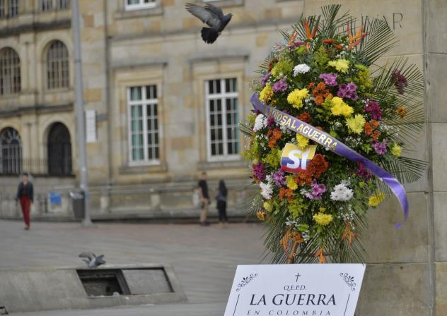 """A wreath placed before the statue of Simón Bolívar in Bogota's main square celebrates the peace accord between the Colombian government and the FARC leftist guerrilla group. The ribbon on the wreath says """"Farewell to War"""" in Spanish; the sign beneath r"""