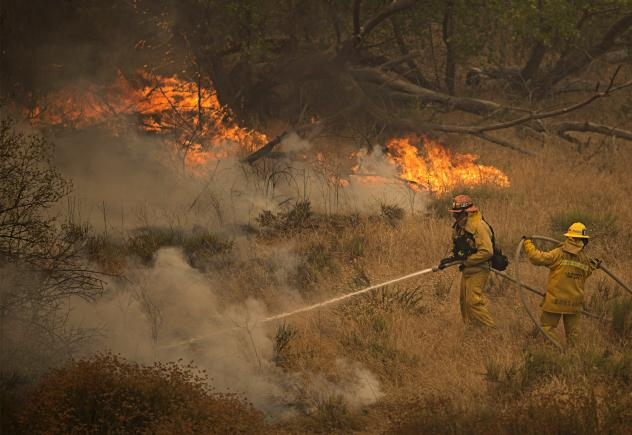 Firefighters battle part of the Sand Fire after flames jumped across a road in Santa Clarita, Calif., on Sunday. As the blaze changed direction multiple times over the weekend firefighters were forced to retreat and thousands of people have been evacuate