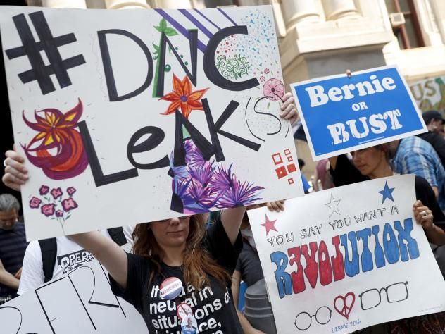 Demonstrators held signs outside the Democratic National Convention on Monday in Philadelphia. On Sunday, Debbie Wasserman Schultz, announced she would step down as DNC chairwoman at the end of the party's convention, after thousands of internal DNC emai
