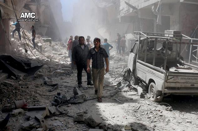 Syrian citizens inspect damaged buildings after airstrikes hit Aleppo, Syria in July, in a photo provided by the Syrian anti-government activist group Aleppo Media Center (AMC).
