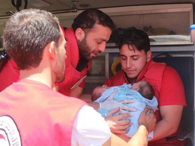 A Syrian Red Crescent team works to evacuate the conjoined twins to a hospital in Damascus on Friday.