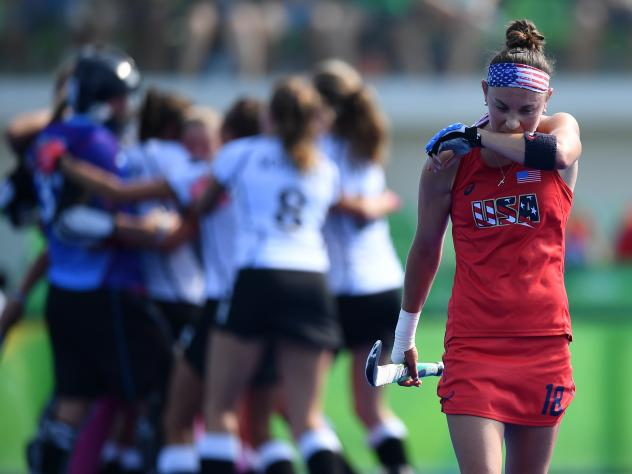 Michelle Kasold of the U.S. leaves the pitch as Germany's players celebrate their win in a women's quarterfinal field hockey match at the Rio 2016 Summer Olympics.