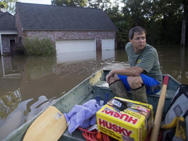 Louisiana resident David Key rides away after reviewing the damage to his home. Federal officials have expanded a disaster declaration after flooding in the state damaged tens of thousands of homes and left nine people dead.