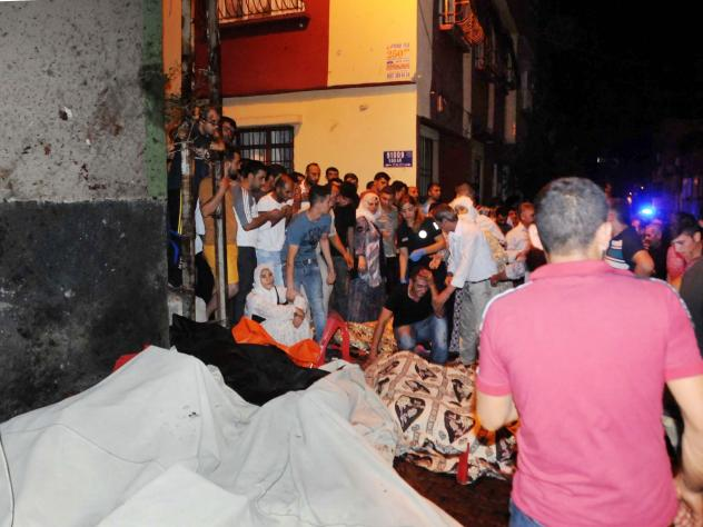 People react after an explosion in Gaziantep, southeastern Turkey. Gaziantep province Gov. Ali Yerlikaya said the deadly blast, during a wedding near the border with Syria, was a terror attack.