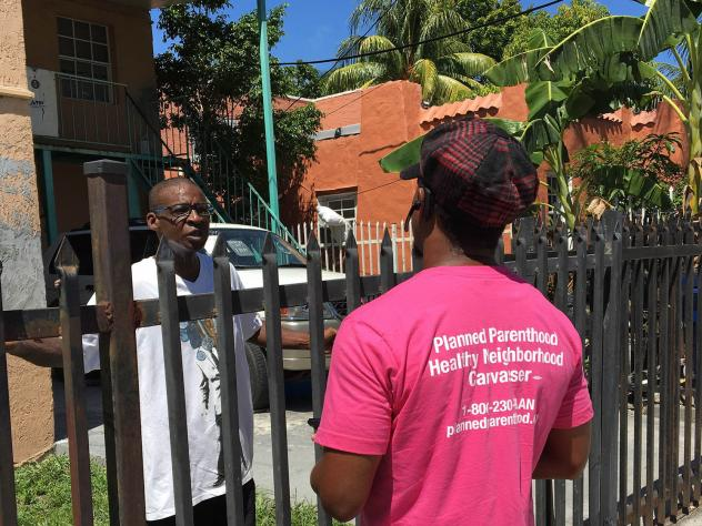 Lenroy Watt (left) and Blair Brown, both Planned Parenthood canvassers, share information about mosquito control, family planning and the risks of Zika in their informal neighborhood meetings.