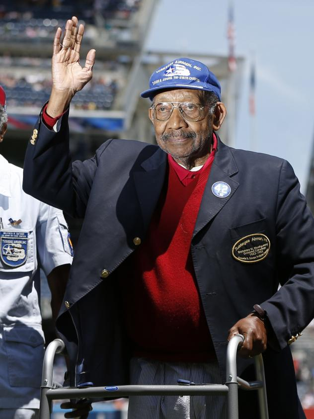 In June 2013, Tuskegee Airman Dabney Montgomery waves to the crowd as he is introduced before the start of a baseball game in New York.