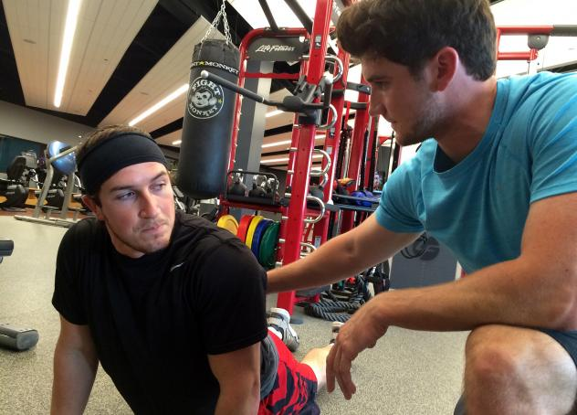 Jake Middleton (right) coaches his brother, Justin, on the cobra pose, which he says can help gamers improve their posture.