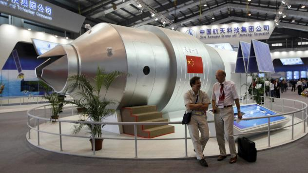 Visitors stand beside a model of the Tiangong-1 space lab in 2010, at the 8th China International Aviation and Aerospace Exhibition in Zhuhai, China. The real Tiangong-1 was launched into space in 2011 and will be returning to Earth next year — with so