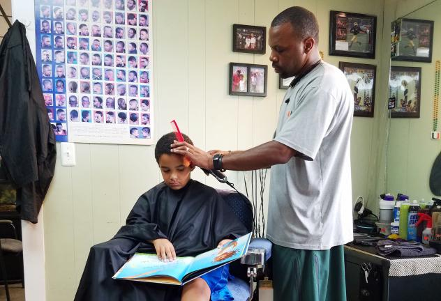 Joziah and Jozef read to their barbers at the Fuller Cut in Ypsilanti, Mich. As part of the barbershop's literacy program, children get $2 off their cut for reading a book to their barber.