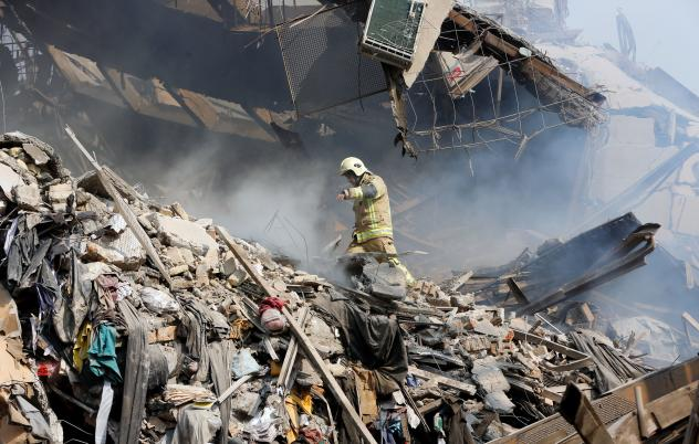 Firefighters stand outside the rubble of the Plasco building on Thursday. Firefighters, soldiers and other emergency responders dug through the ruins of Tehran's oldest high-rise, looking for survivors.
