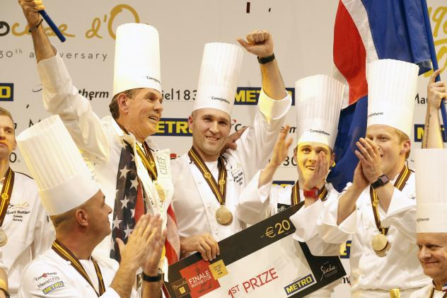"""U.S. chef Mathew Peters (center), celebrates on the podium with teammates after winning the """"Bocuse d'Or"""" trophy, in Lyon."""