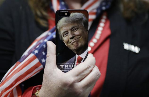 A woman holds up her cellphone before a rally with then presidential candidate Donald Trump in Bedford, N.H., in September.